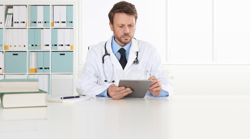 Doctor writing prescription at desk in medical office with digital tablet, copy space and web banner stock photo