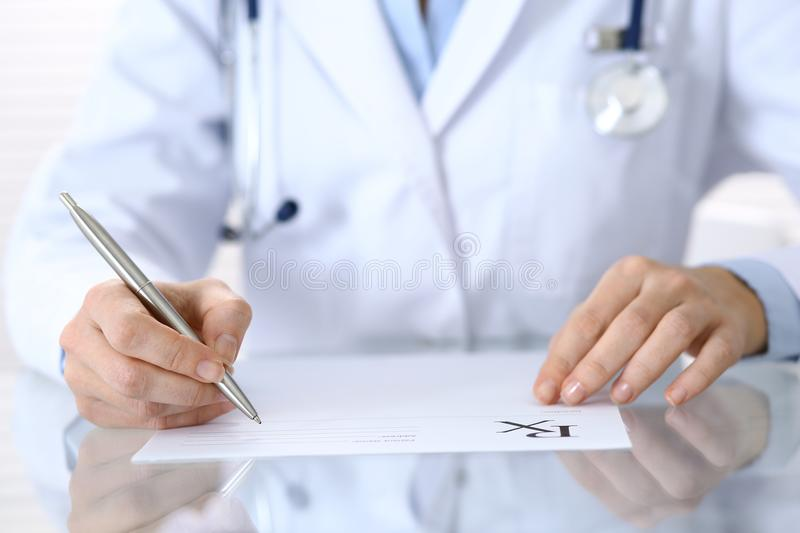 Doctor writing prescription form while sitting at glass desk in hospital, closeup view. Healthcare, insurance an. D excellent service in medicine concept stock photography
