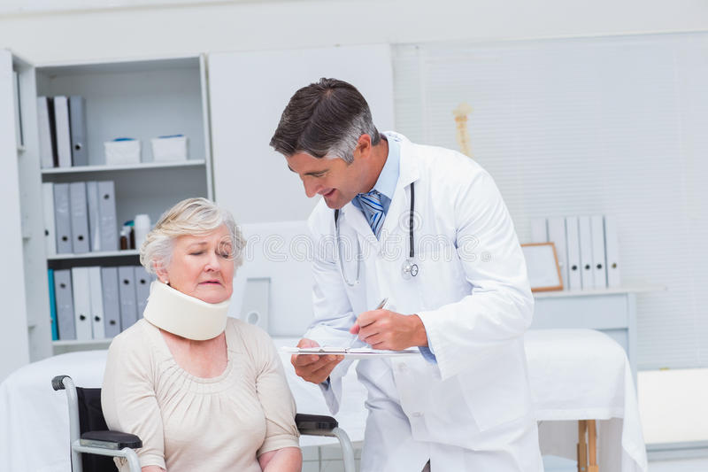 Doctor writing prescription for patient wearing neck brace. Male doctor writing prescription for patient wearing neck brace in clinic stock images