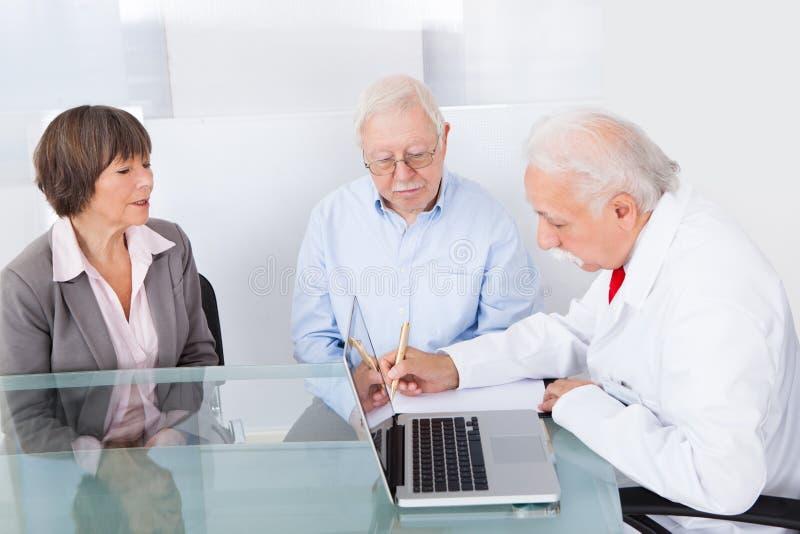 Doctor writing prescription for senior couple stock images
