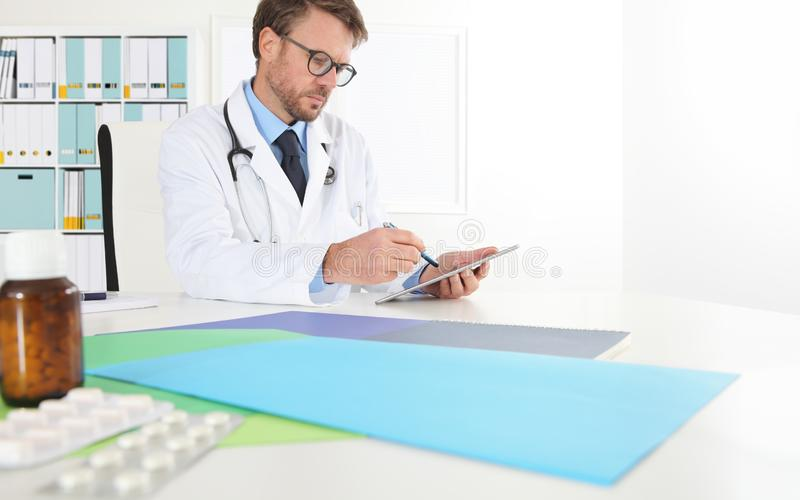 Doctor writing prescription used digital tablet at desk in medical office with drugs in the foreground, copy space web banner stock photography
