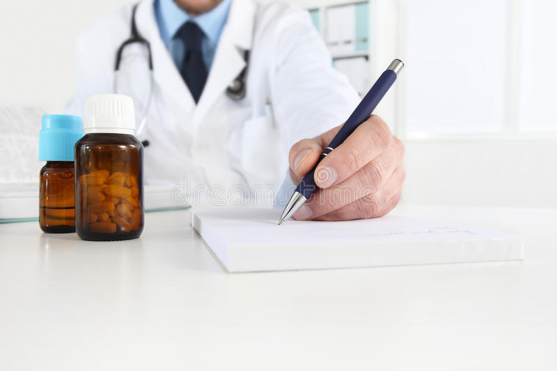 Doctor writing RX prescription in medical office with drugs royalty free stock images