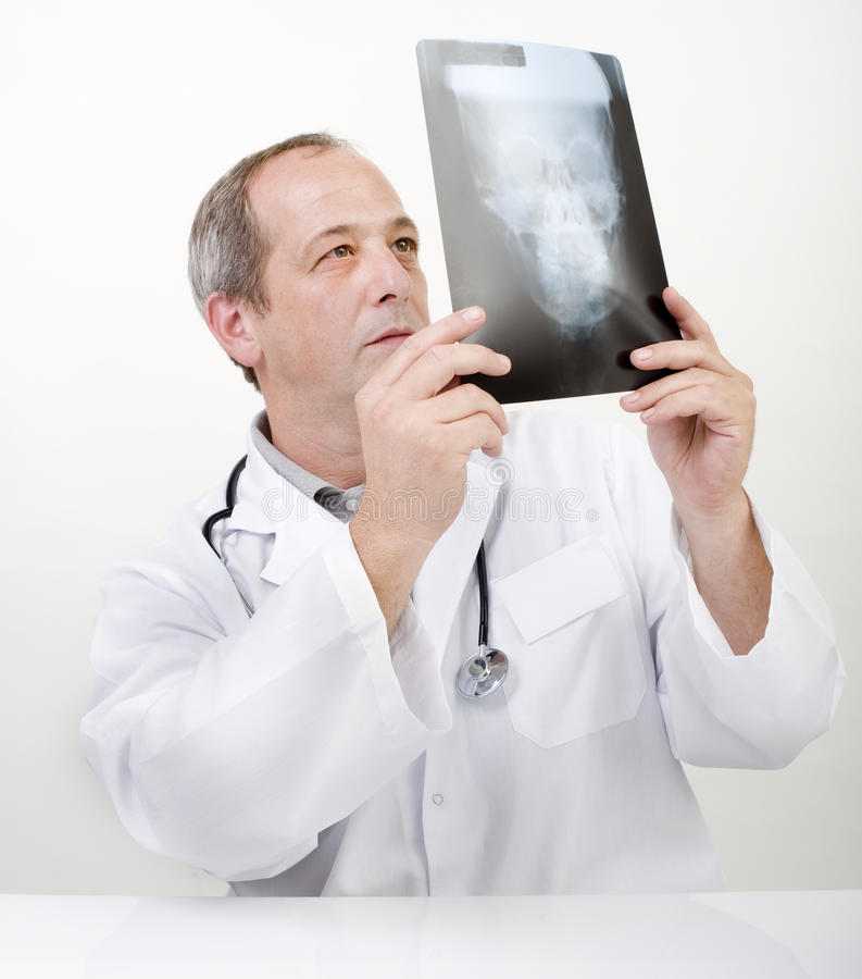 Doctor xray. Doctor looking at xray image of skull stock photography