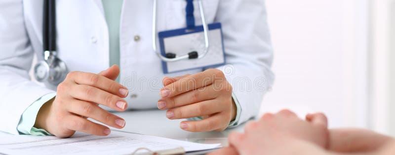 Doctor y el hablar paciente mientras que se sienta en el escritorio en la oficina del hospital, primer de manos humanas Medicina  foto de archivo libre de regalías
