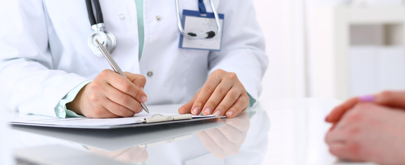 Doctor y el hablar paciente mientras que se sienta en el escritorio en la oficina del hospital, primer de manos humanas Medicina  imagenes de archivo