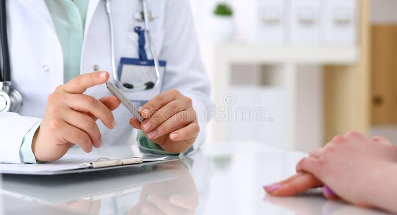 Doctor y el hablar paciente mientras que se sienta en el escritorio en la oficina del hospital, primer de manos humanas Medicina  imagen de archivo