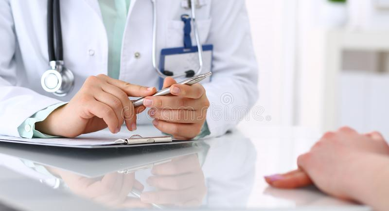 Doctor y el hablar paciente mientras que se sienta en el escritorio en la oficina del hospital, primer de manos humanas Medicina  fotos de archivo libres de regalías