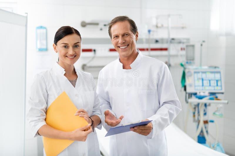 Doctor y enfermera de risa que presentan en el sitio de hospital imagenes de archivo