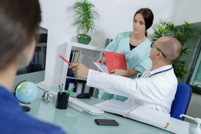 Doctor y enfermera durante la consulta con el paciente imágenes de archivo libres de regalías