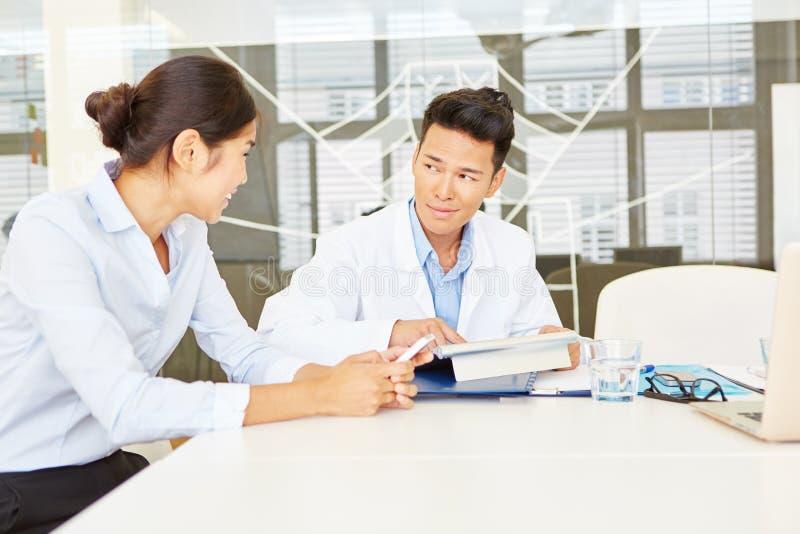 Doctor y enfermera en la reunión del equipo foto de archivo
