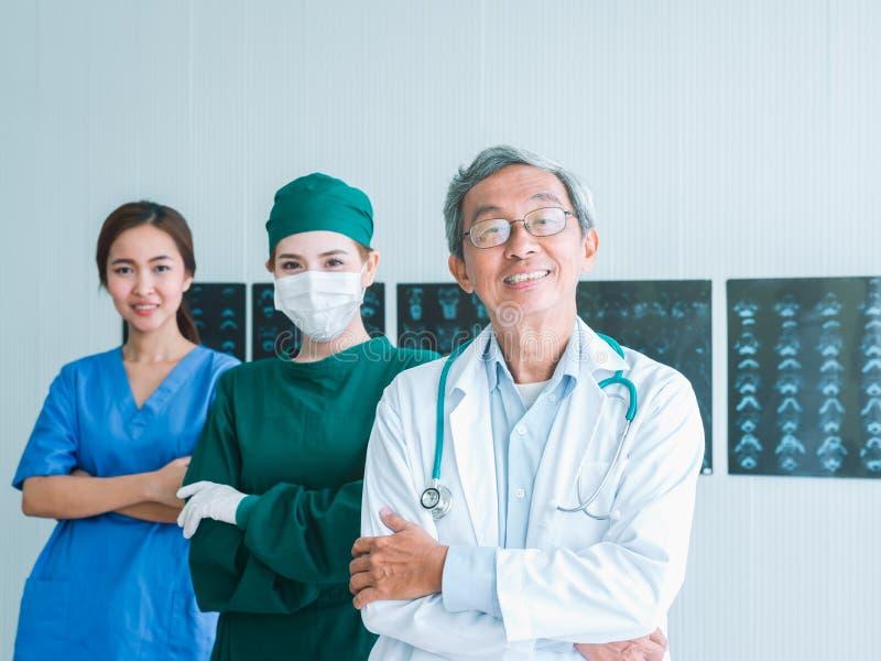 Doctor y equipo mayores con la enfermera y el retrato femenino del doctor Surgeon en oficina en el hospital imágenes de archivo libres de regalías