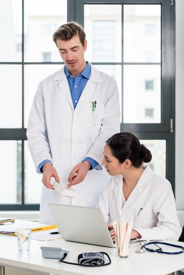 Doctor y farmacéutico que comprueban la información sobre un ordenador portátil en un hospital moderno fotos de archivo