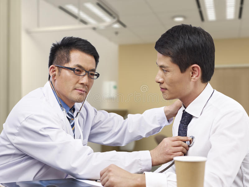 Doctor y paciente asiáticos imagenes de archivo
