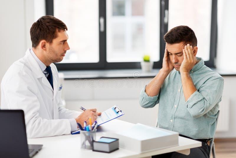 Doctor y paciente masculino que tienen dolor de cabeza en la clínica fotografía de archivo