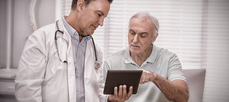 Doctor y paciente mayor que usa la tableta digital fotografía de archivo
