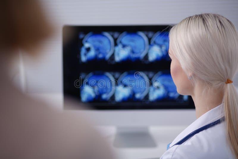 Doctor y paciente que discuten algo mientras que se sienta en la tabla Concepto de la medicina y de la atención sanitaria Doctor  fotografía de archivo