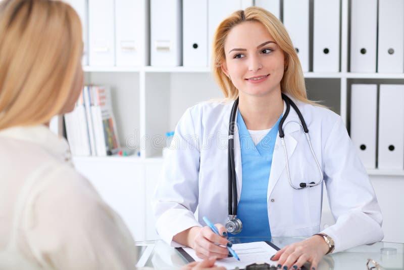 Doctor y paciente que discuten algo mientras que se sienta en la tabla en el hospital Concepto de la medicina y de la atención sa fotografía de archivo libre de regalías
