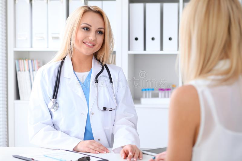Doctor y paciente que discuten algo mientras que se sienta en la tabla en el hospital Concepto de la medicina y de la atención sa fotos de archivo