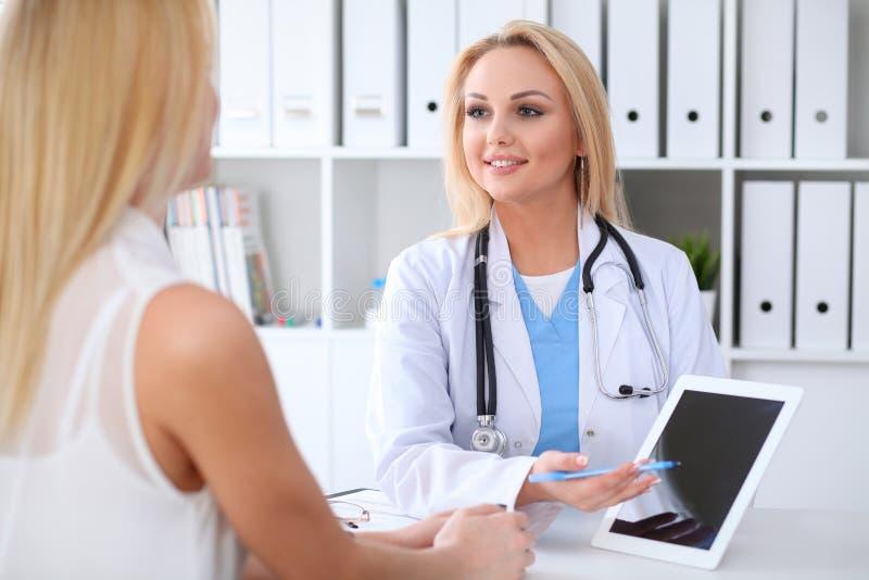 Doctor y paciente que discuten algo mientras que se sienta en la tabla en el hospital Médico que usa la PC de la tableta para imagen de archivo