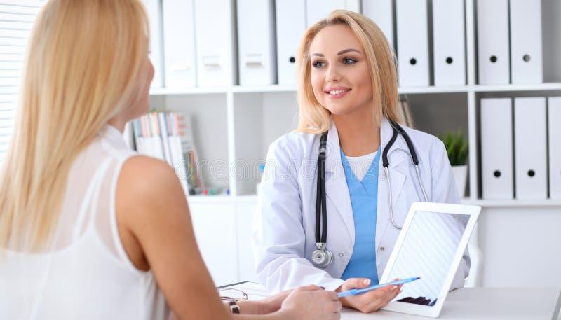 Doctor y paciente que discuten algo mientras que se sienta en la tabla en el hospital Médico que usa la PC de la tableta para foto de archivo