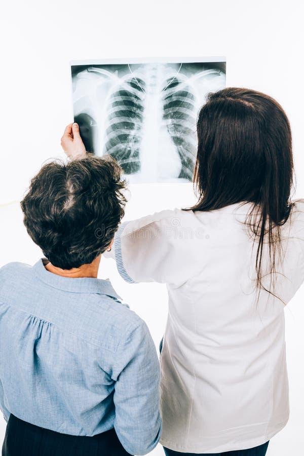 Doctor y paciente que miran la radiografía foto de archivo libre de regalías