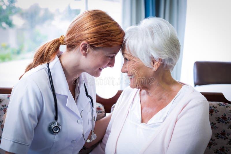 Doctor y paciente sonrientes que parecen cara a cara imagen de archivo libre de regalías