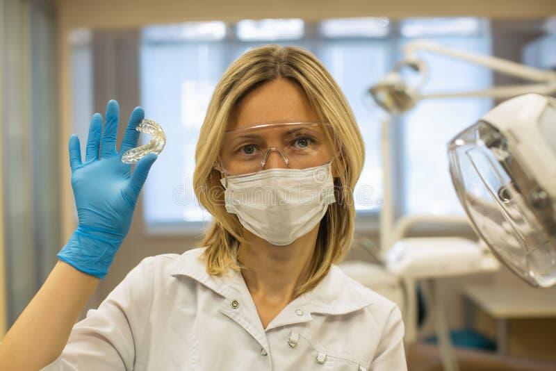 Doctora en odontología muestra un dispositivo extraíble para la alineación de dientes ortopédicos y el adiestramiento de corre fotos de archivo