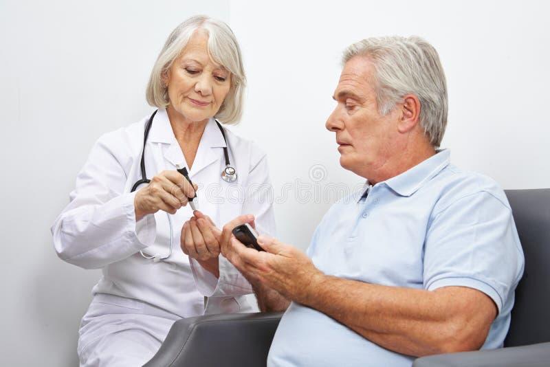 Doctore faisant l'essai de sucre de sang pour l'aîné image stock
