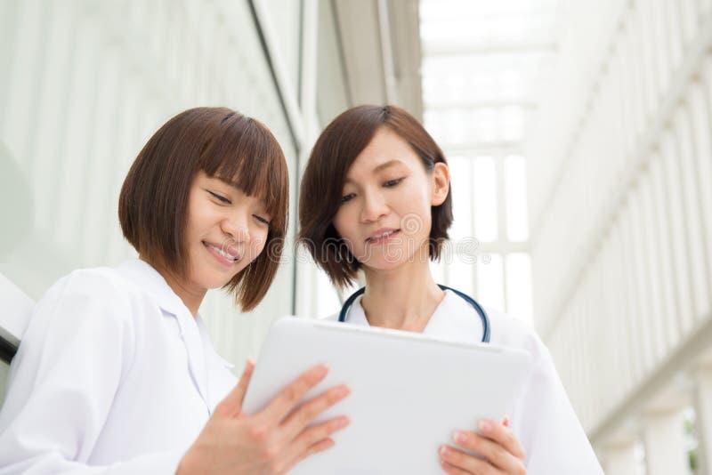 Doctores asiáticos que tienen discusión con la tableta digital de la PC imágenes de archivo libres de regalías