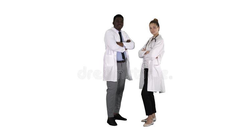 Doctores de la mujer y del hombre con los brazos cruzados en el fondo blanco imagen de archivo libre de regalías
