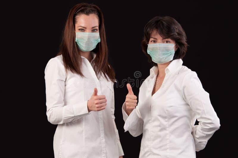 Doctores de sexo femenino amistosos con los pulgares para arriba sobre negro fotografía de archivo libre de regalías
