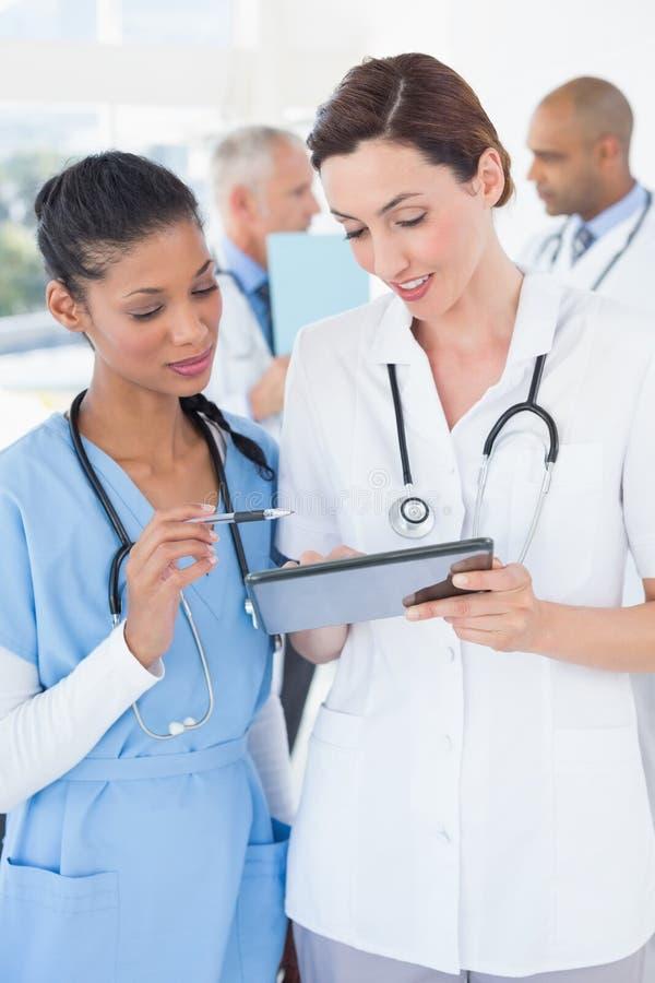 Doctores de sexo femenino hermosos que trabajan así como la tableta imágenes de archivo libres de regalías