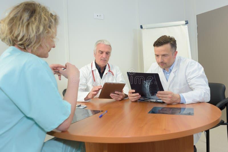 Doctores del equipo que miran el caso especial de los pacientes fotos de archivo libres de regalías