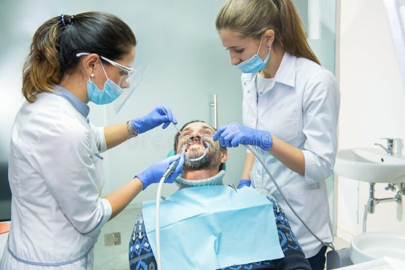 Doctores dentales con el paciente foto de archivo