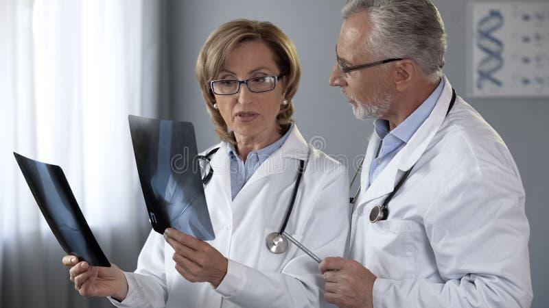 Doctores experimentados que discuten los métodos de tratamiento, comparando radiografías de juntas fotografía de archivo libre de regalías