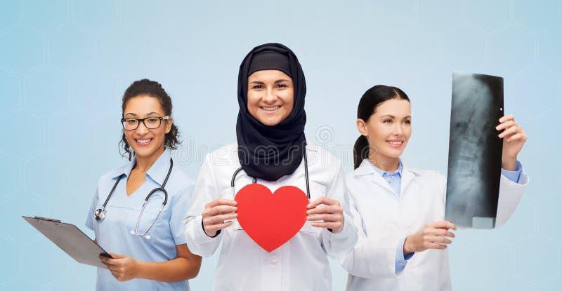 Doctores felices con el corazón, la radiografía y el tablero rojos fotografía de archivo