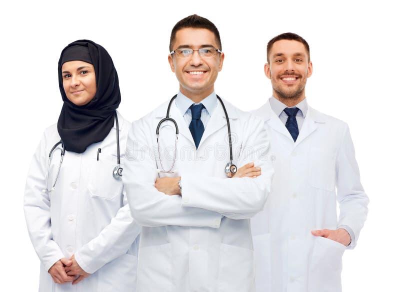 Doctores felices en las capas blancas con los estetoscopios fotos de archivo