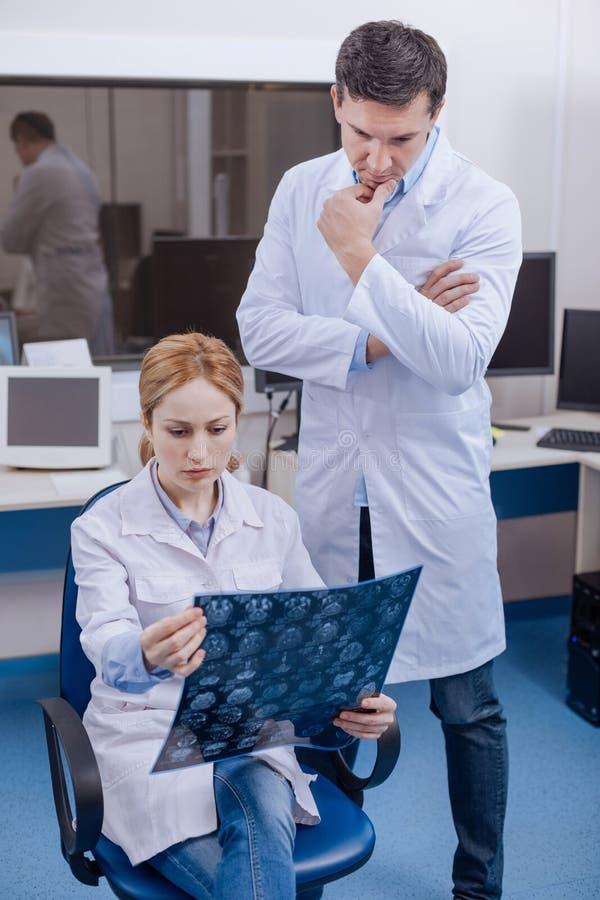 Doctores inteligentes pensativos que trabajan junto imagen de archivo libre de regalías
