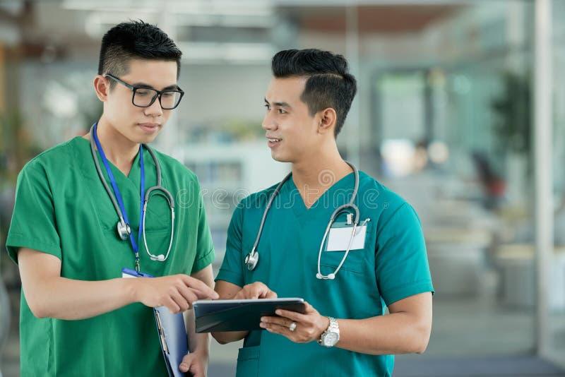 Doctores jovenes que señalan en la tableta en hospital fotos de archivo libres de regalías