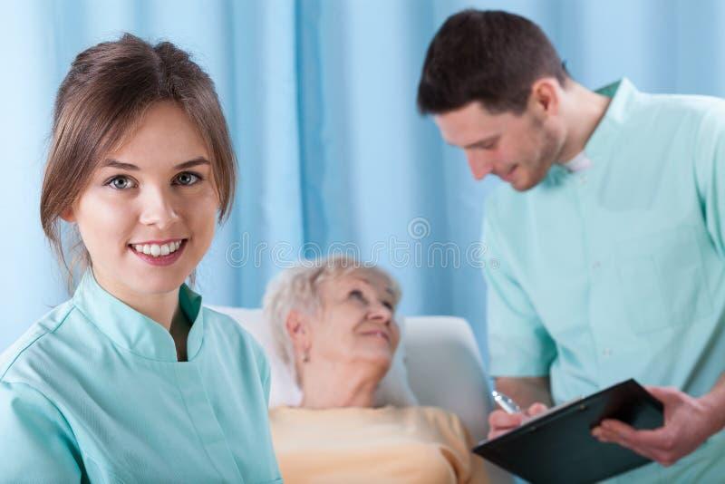 Doctores jovenes y un más viejo paciente fotos de archivo