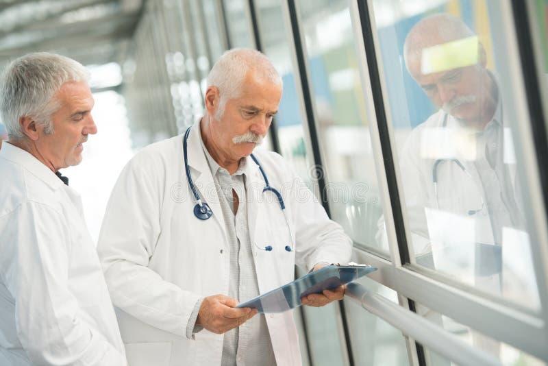 Doctores mayores que hablan con la enfermera fotografía de archivo libre de regalías