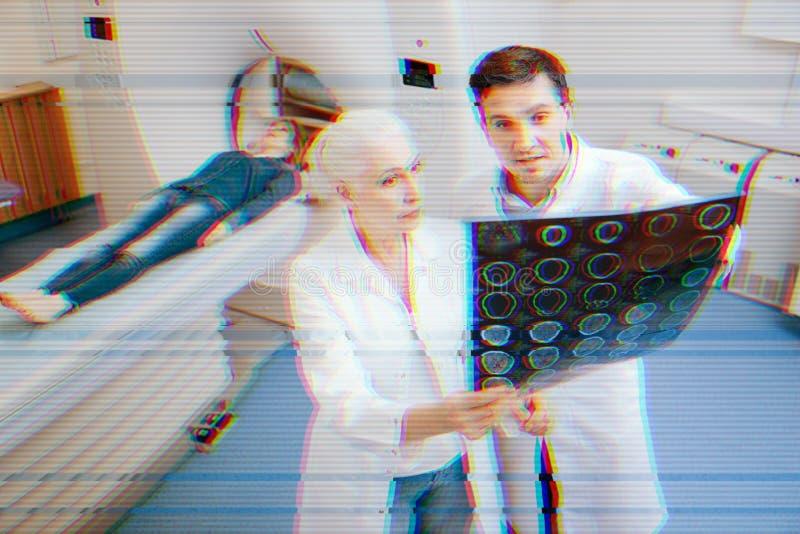 Doctores profesionales que se unen y que discuten los resultados del MRT de su paciente foto de archivo