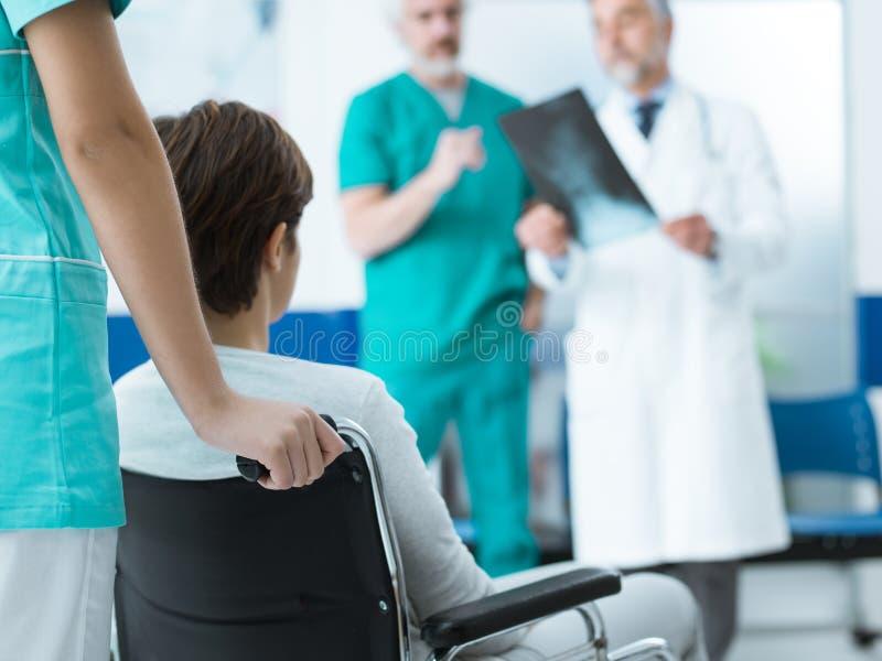 Doctores que comprueban una radiografía paciente discapacitada del ` s fotos de archivo libres de regalías