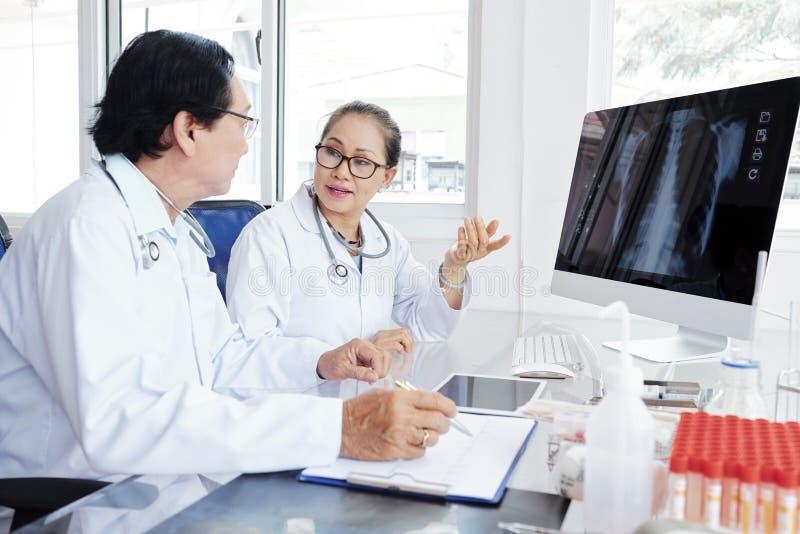 Doctores que discuten el caso de la pulmonía fotografía de archivo