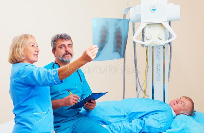Doctores que discuten la radiograma de Roentgen en sitio de la radiografía con el paciente imágenes de archivo libres de regalías