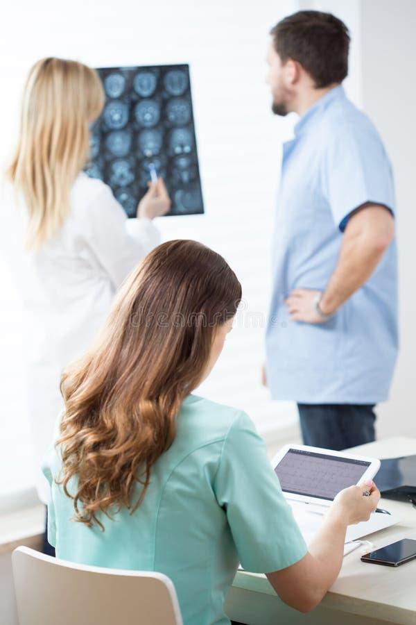 Doctores que leen MRI y el electrocardiograma fotos de archivo