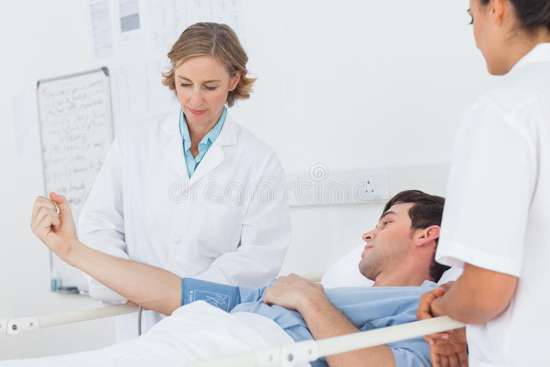 Doctores que miden la presión arterial de un paciente masculino imagen de archivo libre de regalías
