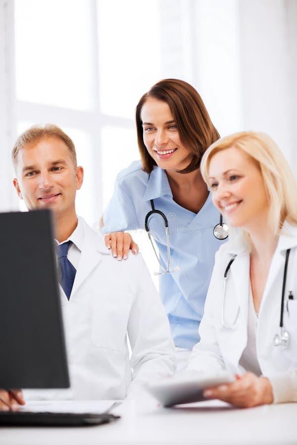Doctores que miran el ordenador en la reunión foto de archivo libre de regalías