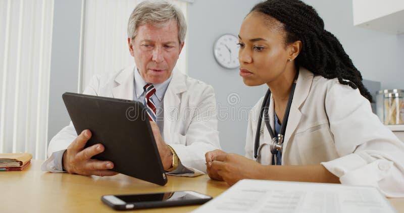 Doctores que trabajan junto en la oficina fotografía de archivo