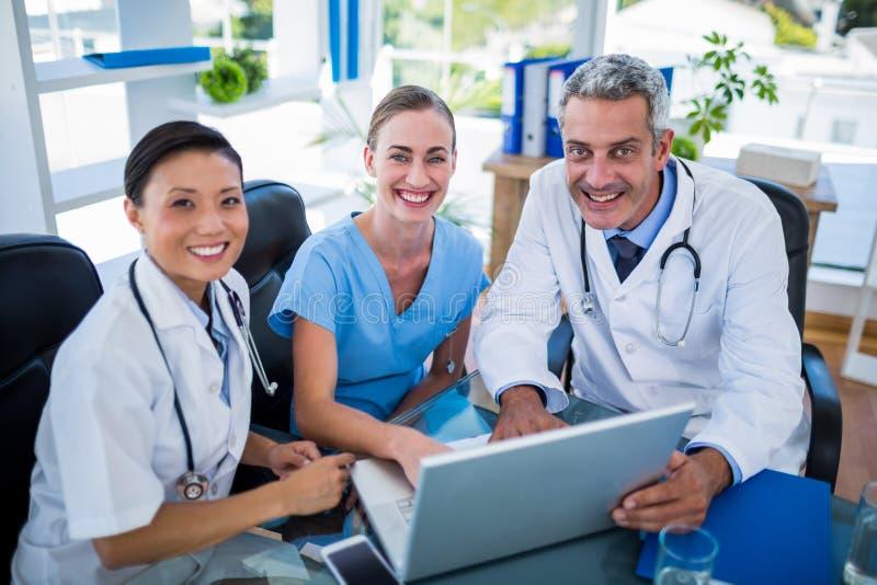 Doctores y enfermera que miran el ordenador portátil y que sonríen en la cámara imagen de archivo libre de regalías